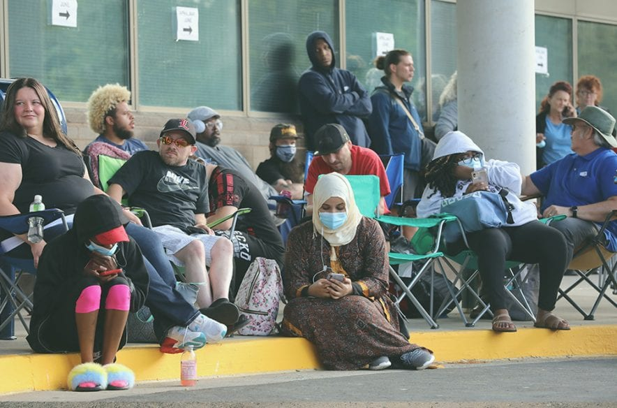 Hundreds of unemployed Kentucky residents are pictured waiting in long lines outside the Kentucky Career Center in June 2020. Extra federal unemployment benefits are set to end Sept. 6, but some states are announcing an end to the extra benefits even earlier.