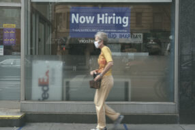 A hiring sign is displayed in a store window in New York City on Aug. 19, 2021. Jobless claims recently increased for the first time in five weeks, while a new unemployment cliff looms on Sept. 6.