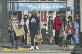 Photo of shoppers outside in a city to accompany story about holiday shopping trends