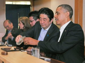 From left: Japan's Prime Minister Shizo Abe fills the glass of U.S. President Barak Obama during a dinner at Sukiyabashi Jiro sushi restaurant in Tokyo's Ginza district on April 23, 2014.