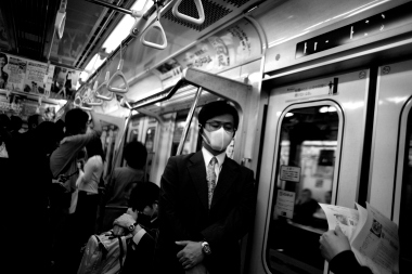 "A Japanese ""salary man"" company employee, wearing a germ protecting mask and headphones, makes his morning commute to the office on the Tokyo subway in May 2006. The photo was part of a photo essay that was awarded the 1st prize in Daily Life Stories category of the World Press Photo 2007 contest."
