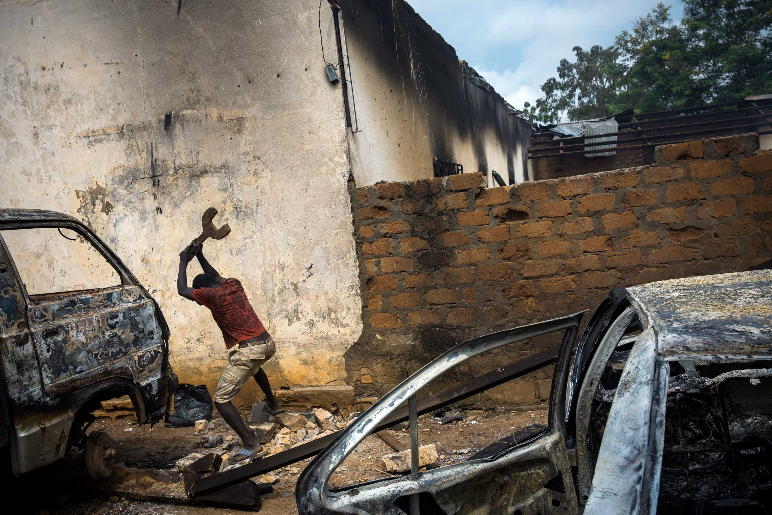 BanguiA Christian man is destroying burn out cars in rage, next to a looted mosque that was set on fire earlier, in the capital Bangui.