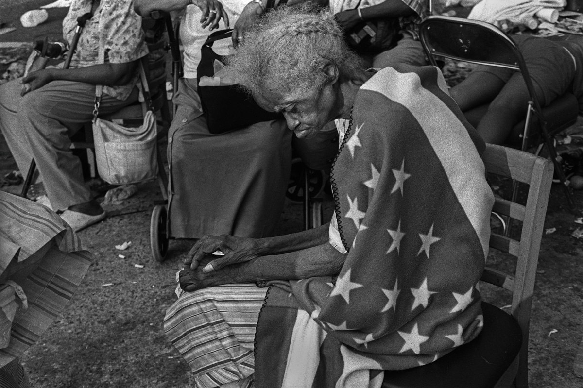 New Orleans, LouisianaSeptember 2, 2005Hurricane Katrina: 84-year old Milvertha Hendricks wrapped in an American flag blanket after spending five days on the street at the Convention Center. She was not evacuated until the next day.PHOTOGRAPH by ALAN CHIN