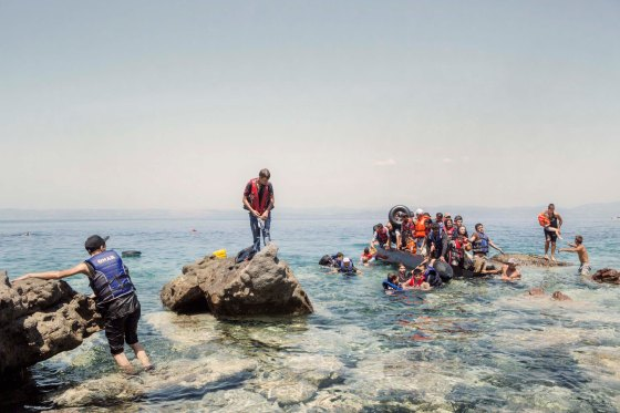 A boat carrying Syrians and people of other nationalities is dragged ashore by two local farmers. The boat had started to leak, forcing a small group of people to swim to the beach in Lesbos, Greece, Aug. 5, 2015.