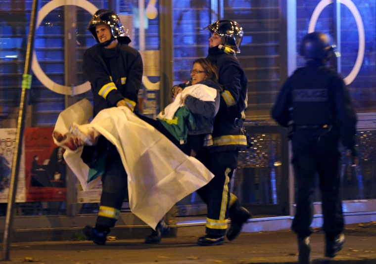 French fire brigade members aid an injured individual near the Bataclan concert hall following fatal shootings in Paris on Nov. 13, 2015.