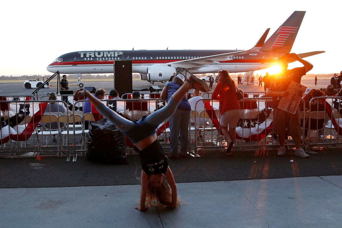 Rylee Jacobs, 10, does cartwheels in front of the plane of U.S. Republican presidential candidate Donald Trump after Trump spoke at a campaign rally in Sacramento