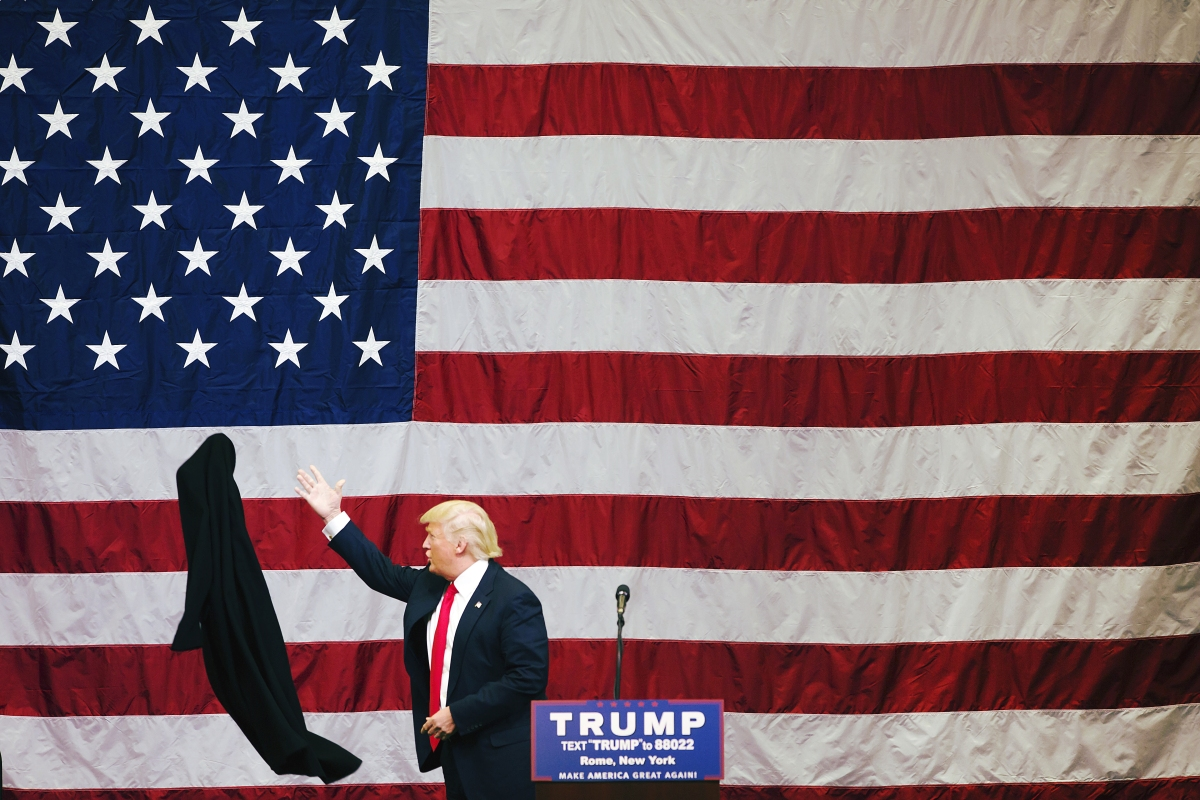 Donald Trump tosses his coat aside during a fly-in campaign stop at the Griffiss International Airport in Rome, N.Y.