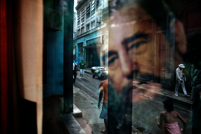 A window reflects an image of Fidel Castro in a working-class Havana neighborhood that attracts few tourists.