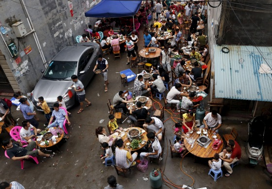 People eat dog meat at a dog meat restaurant district on the day of local dog meat festival in Yulin