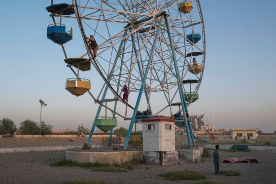 Young boys climb a broken-down Ferris Wheel in order to give a friend a quarter of a revolution ride, in a dilapidated playground in the capital of Helmand Province, Lashkar Gah.