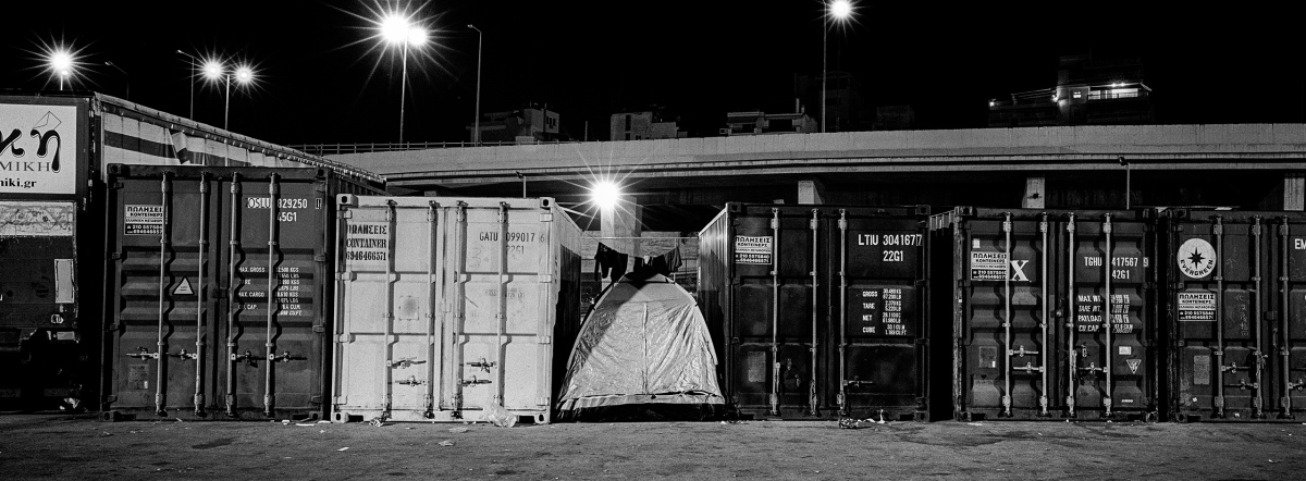 A tent sits among containers at the Greek port of Piraeus, near where refugees and migrants live in a temporary camp.