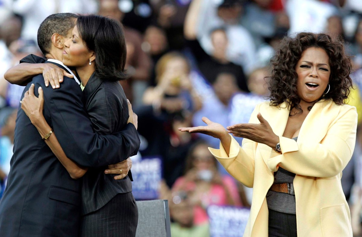 Barack Obama and Michelle Obama embrace as Oprah Winfrey campaigns with them during a rally at Williams Brice Stadium in Columbia, S.C., Dec. 9, 2008.