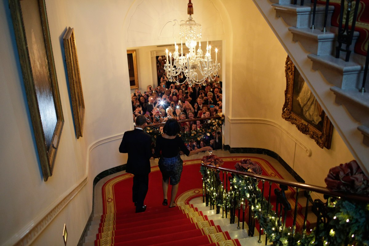 Barack Obama and Michelle Obama descend the White House staircase to a packed audience attending a Christmas Party at the White House, Dec. 12, 2012.