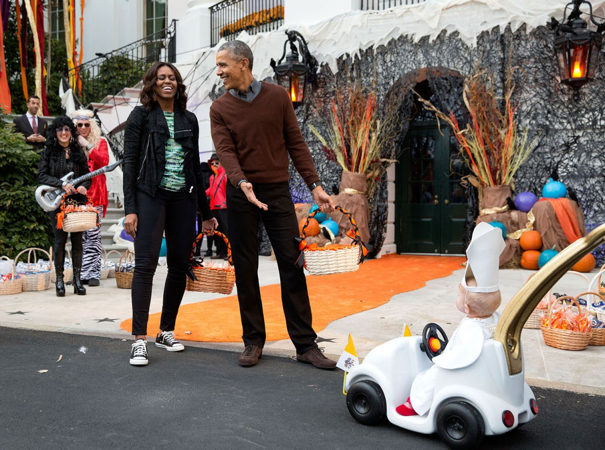 The President and First Lady react to a child in a pope costume and mini popemobile as they welcomed children during a Halloween event on the South Lawn of the White House in Washington, D.C., Oct. 30, 2015.