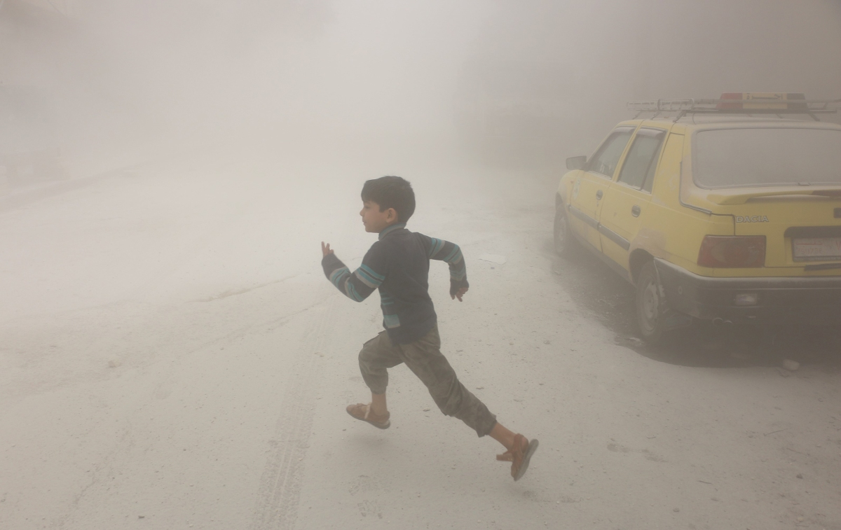 A boy runs after airstrikes conducted by Syrian government forces hit a neighborhood in rebel-held Aleppo on April 24, 2016.