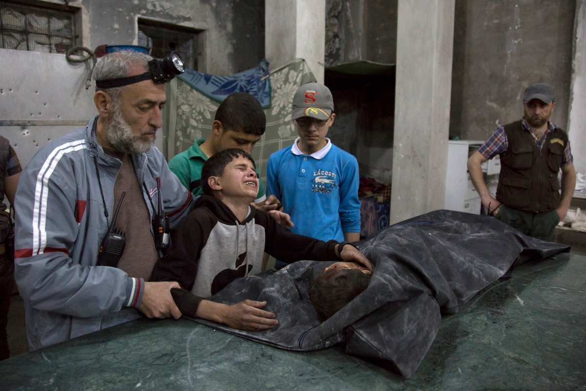 A boy is comforted as he cries next to the body of a relative who died in a reported airstrike in a rebel-held neighborhood of Aleppo on April 27, 2016.
