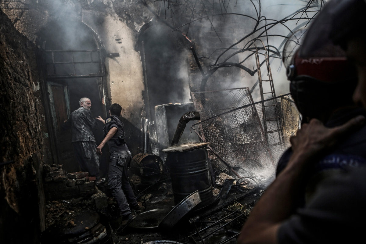 First-responders attempt to stop Abu Soubhi from entering his home following an airstrike in the rebel-held area of Douma, on the outskirts of Damascus, on Sept. 11, 2016.