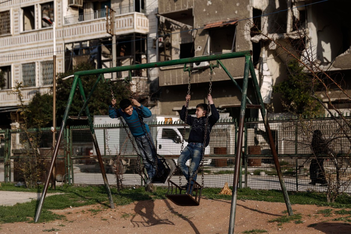 Boys play on a swing set during a halt in fighting in Douma, in the region of Eastern Ghouta outside Damascus, on Feb. 27, 2016.