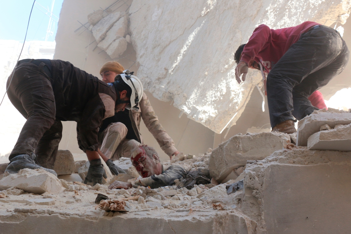 Rescue workers and residents try to pull a man out from under the rubble of a building following a reported airstrike on the rebel-held neighborhood of Salhin in Aleppo on March 11, 2016.