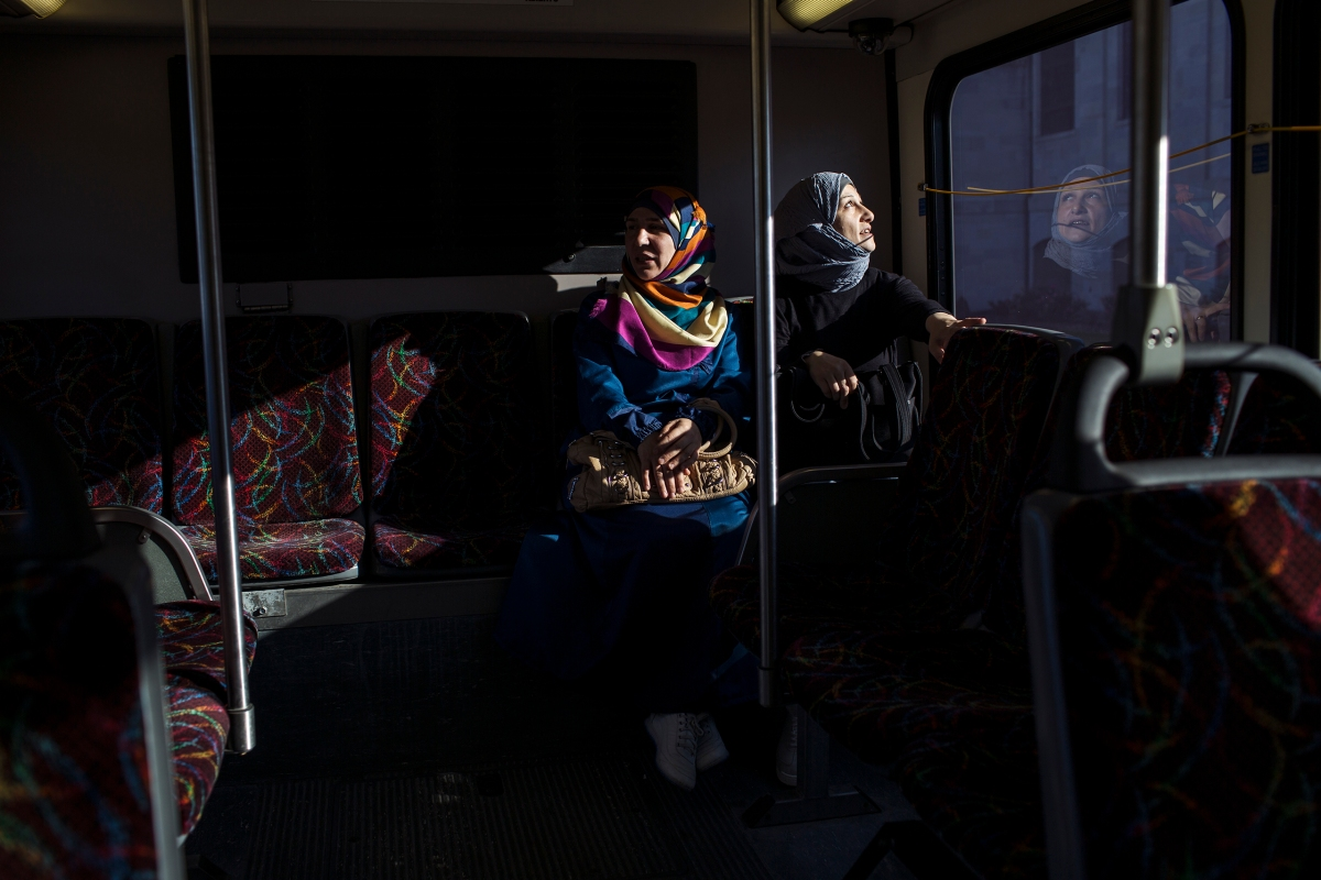 Ghazweh and her friend, Mumena El Ali, ride the bus while on their way to ESL class at a community college.