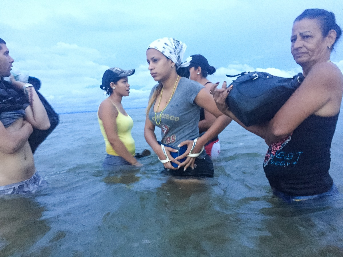 Liset and Marta, with locals who help guide migrants, prepare to board a boat at dawn on June 6, traveling from Necoclí to Capurganá, in Colombia, as they close in on Panama's border.