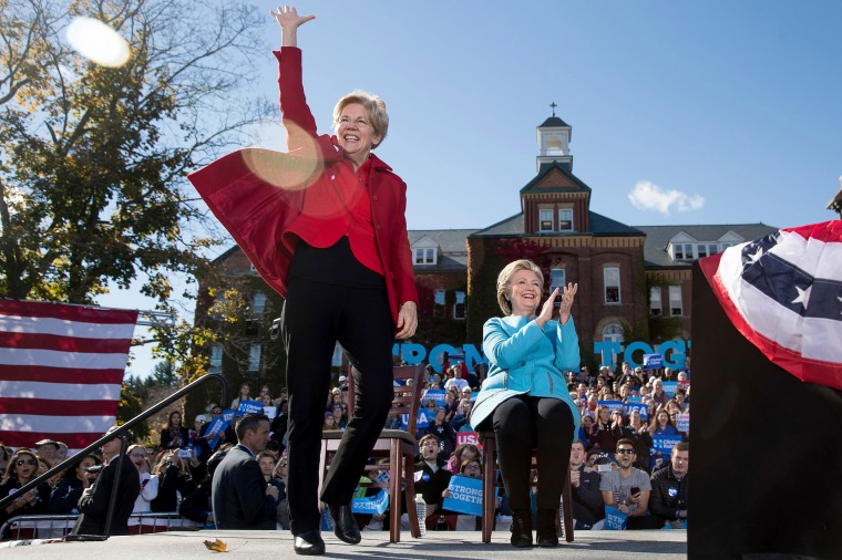 Sen. Elizabeth Warren, accompanied by Hillary Clinton, waves as she takes the stage at a rally, on Oct. 24, 2016, in Manchester, N.H.