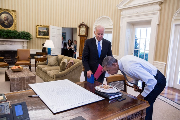 President Barack Obama blows out candles on birthday cupcakes brought to him by Vice President Joe Biden in the Oval Office, Aug. 4, 2016. (Official White House Photo by Pete Souza)This official White House photograph is being made available only for publication by news organizations and/or for personal use printing by the subject(s) of the photograph. The photograph may not be manipulated in any way and may not be used in commercial or political materials, advertisements, emails, products, promotions that in any way suggests approval or endorsement of the President, the First Family, or the White House.