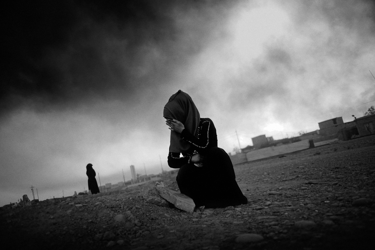 A young woman in grief, cries at her mother grave in the outskirts of the city Qayyara, south of Mosul. She was killed in an airstrike by coalition forces as they backed up Iraqi forces retaking the city from IS. Before leaving the city, IS destroyed all the tombstones in the graveyard. The dense plumes of smoke are emanating from multiple sites about 30 miles (50 km) south of Mosul. The fires were deliberately set by ISIS militants before abandoning the city. The smoke has been persistent over the past three months, blotting out the sun hours before nightfall and creating major health issue for mainly the children in the area.