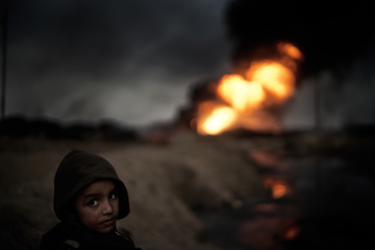 A small boy watches one of the estimated 19 oil wells which has been set at fire by IS in the city Qayyara, south of Mosul. The dense plumes of smoke are emanating from multiple sites about 30 miles (50 km) south of Mosul. The fires were deliberately set by ISIS militants before abandoning the city. The smoke has been persistent over the past three months, blotting out the sun hours before nightfall and creating major health issue for mainly the children in the area.