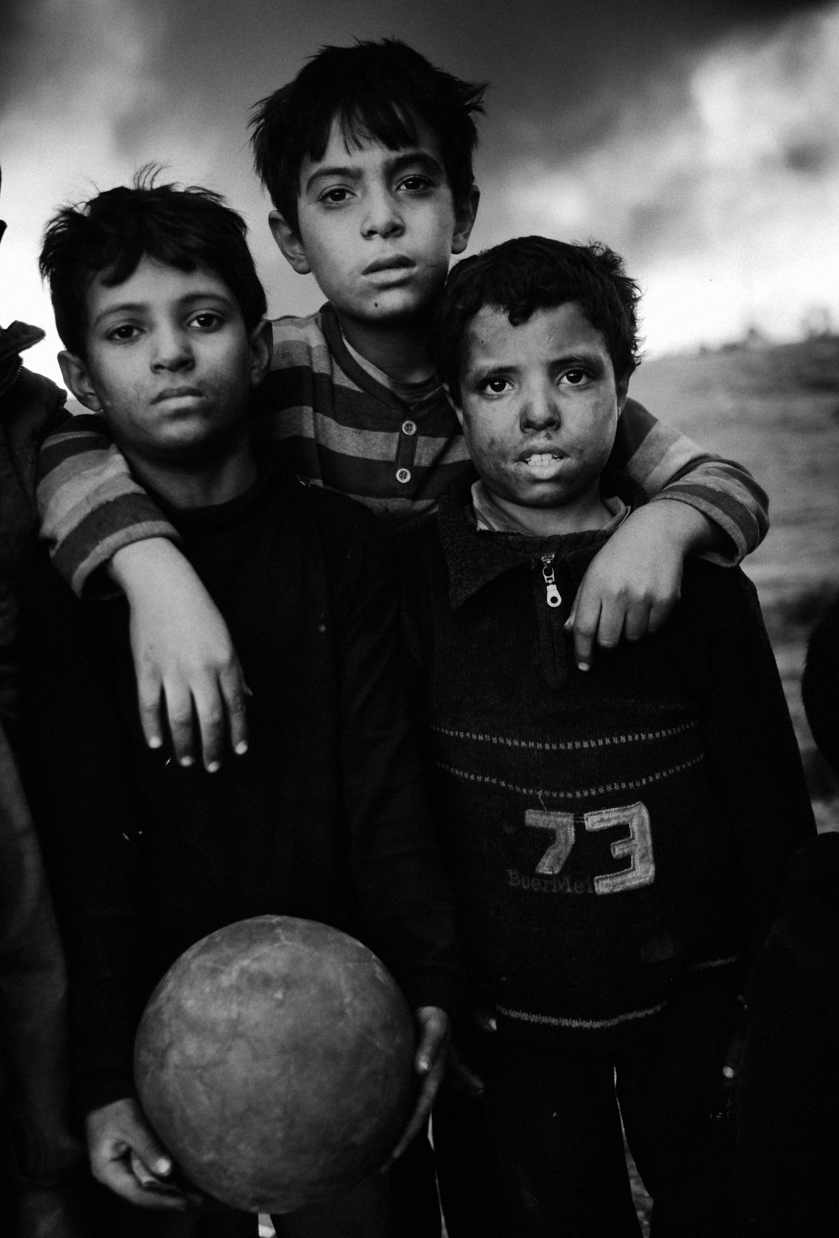 three boys at the football pitch in the city Qayyara, south of Mosul. The dense plumes of smoke are emanating from multiple sites about 30 miles (50 km) south of Mosul. The fires were deliberately set by ISIS militants before abandoning the city. The smoke has been persistent over the past three months, blotting out the sun hours before nightfall and creating major health issue for mainly the children in the area.