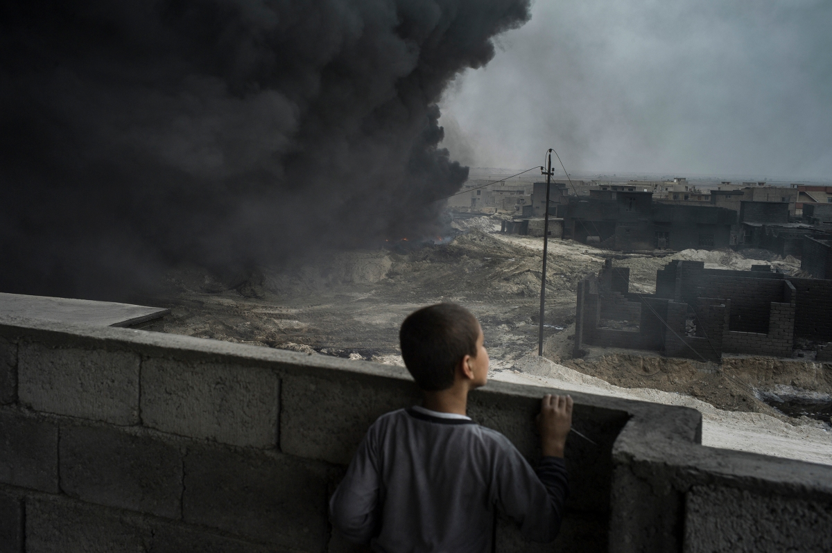 A boy looks out from the rooftop of his house as an oil well burns right next to it in Qayyarah, a town about 60 km south of Mosul. The town fell to ISIS in June 2014 and was recaptured by the Iraqi forces in August 2016, while leaving Qayyarah ISIS burned the oil wells in and around the city.