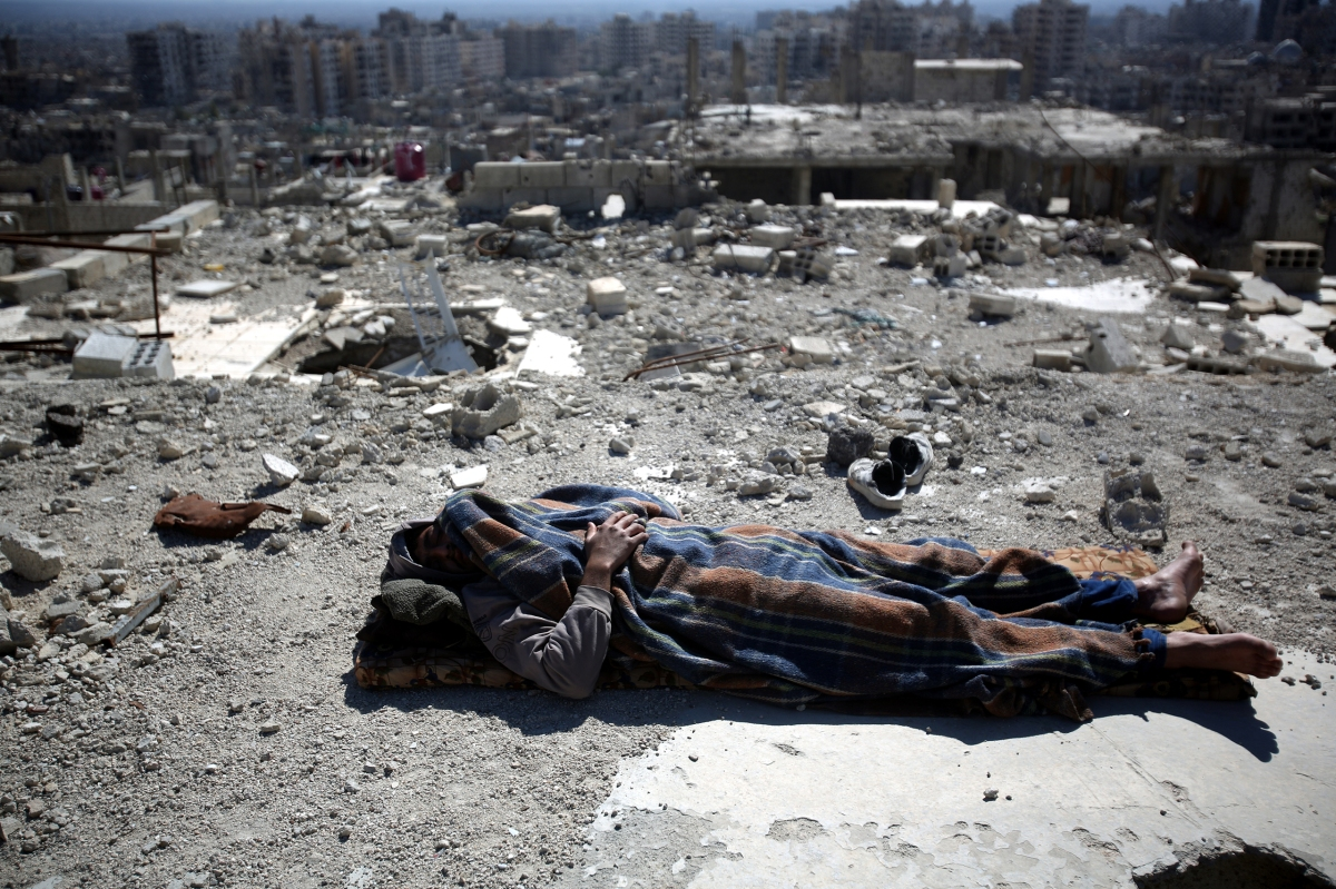 A man sleeps on the roof of a damaged building in the Barzeh neighborhood of Damascus on Feb. 17. Mohammed Badra—EPA