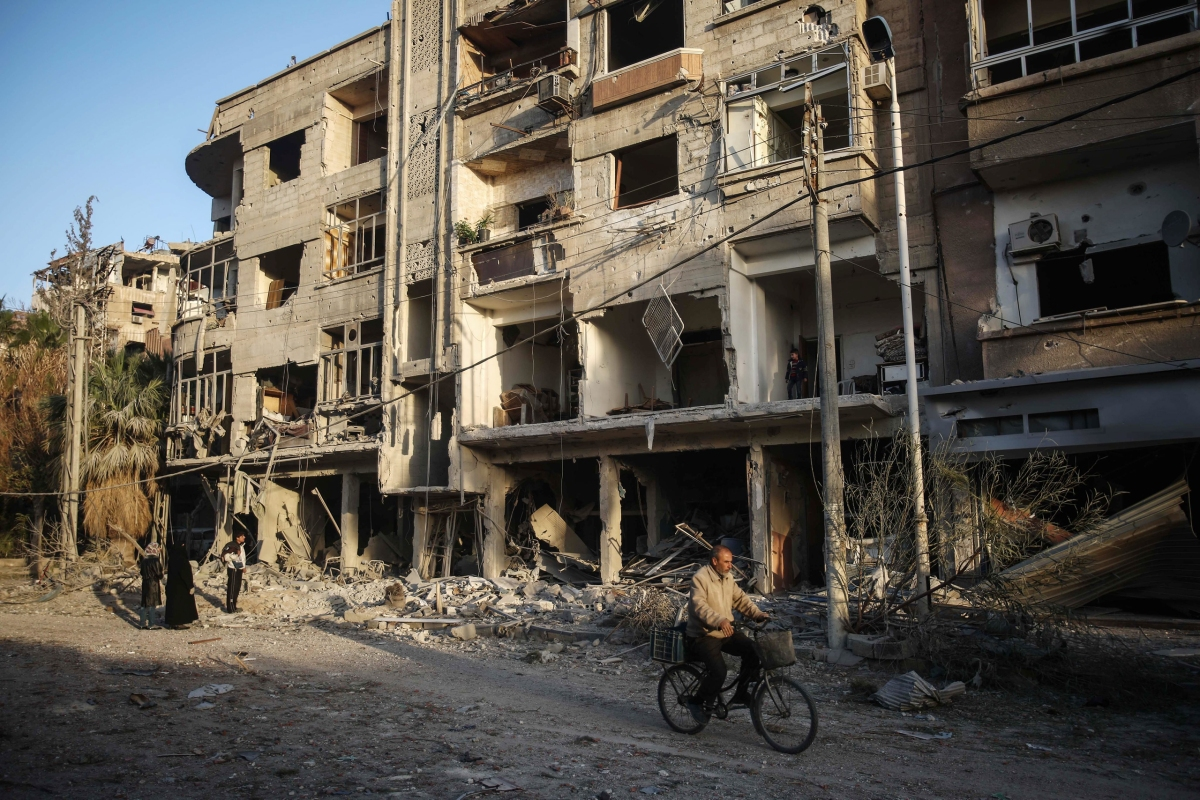 A man cycles past destroyed buildings in Douma on Nov. 22. Mohammed Badra—EPA