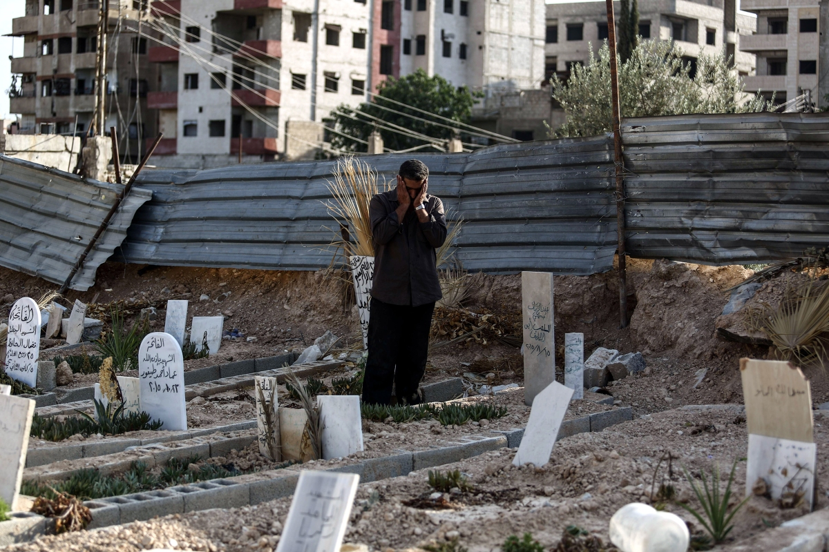 Abu Omar al-Ghoosh, who reportedly lost 17 relatives in a chemical attack, prays at a cemetery in Zamalka on Aug. 21. Mohammed Badra—EPA