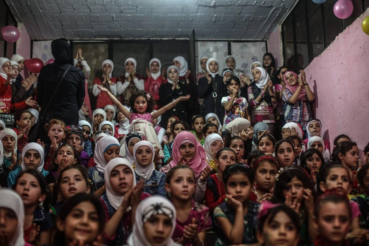 Children listen to songs at an underground amusement park in Erbeen, Eastern Ghouta, on Sept. 16. Mohammed Badra—EPA