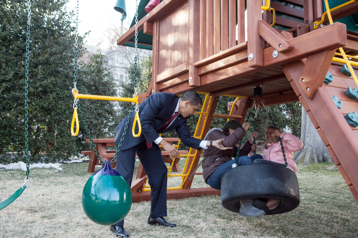 In this official White House photograph, President Barack Obama plays with daughters Malia and Sasha on the new playground swing-set. on the South Lawn of the White House, March 4, 2009.
