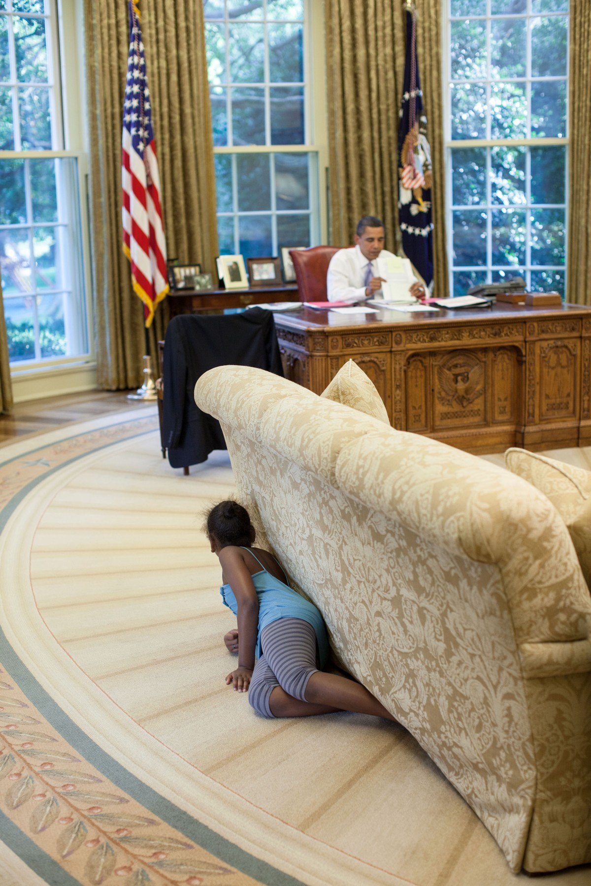 In this official White House photograph, President Barack Obama works at his desk as Sasha Obama sneaks up on him in the Oval Office, Aug. 5, 2009.