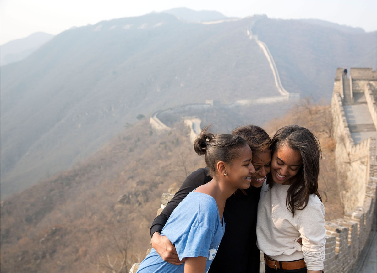 In this official White House photograph, First Lady Michelle Obama hugs daughters Sasha, left, and Malia as they visit the Great Wall of China in Mutianyu, China, March 23, 2014.
