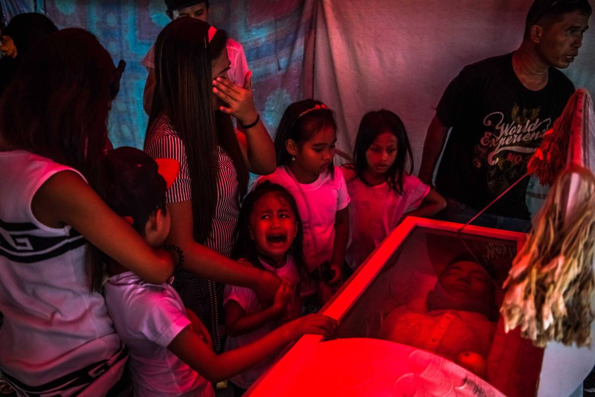 "Jimji, 6, cries out in anguish, saying ""Papa"" as workers move the body of her father, Jimboy Bolasa, 25, for burial, in Manila, Philippines."