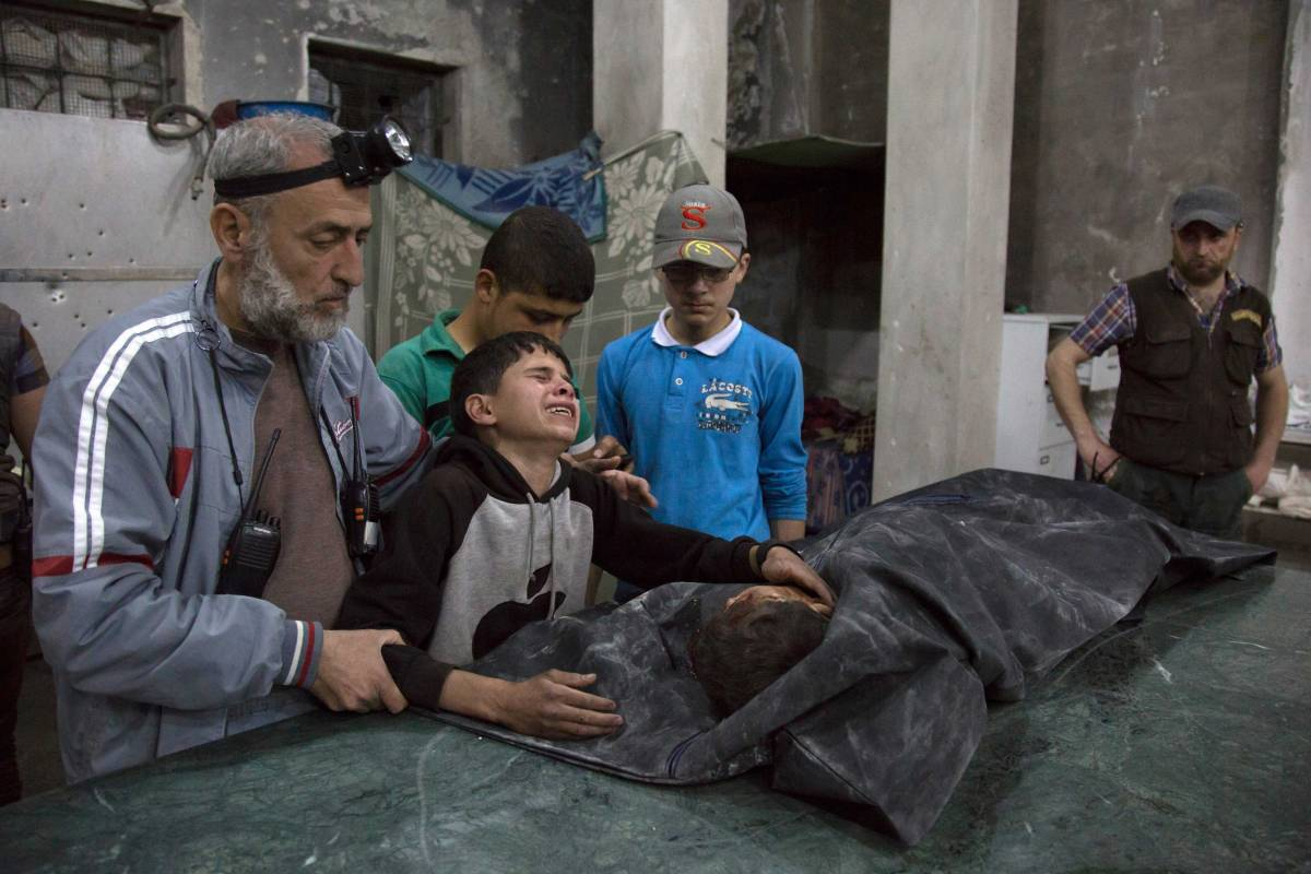 A Syrian boy is comforted as he cries next to the body of a relative who died in a reported airstrike in a rebel-held neighborhood of Aleppo on April 27, 2016.