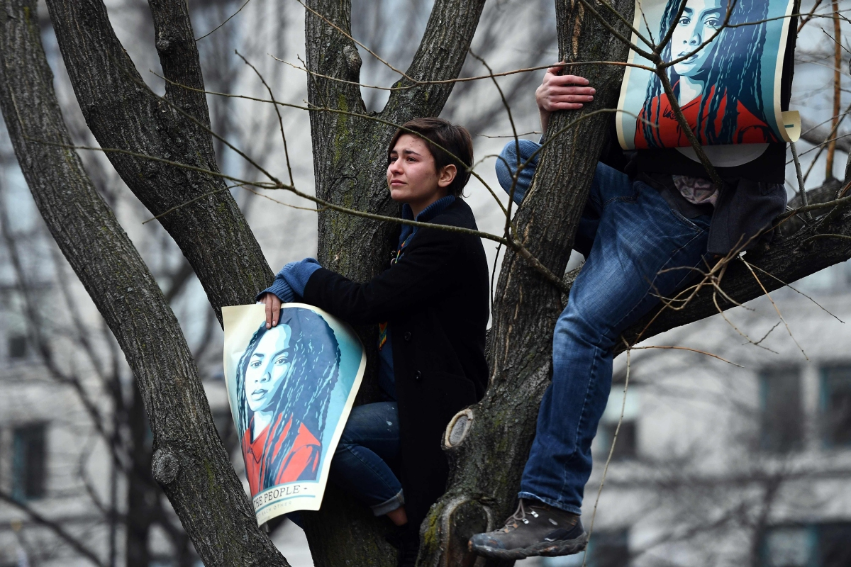 Anti-Trump protesters climb on a tree during a demonstration in Washington, D.C., on Jan. 20, 2017.