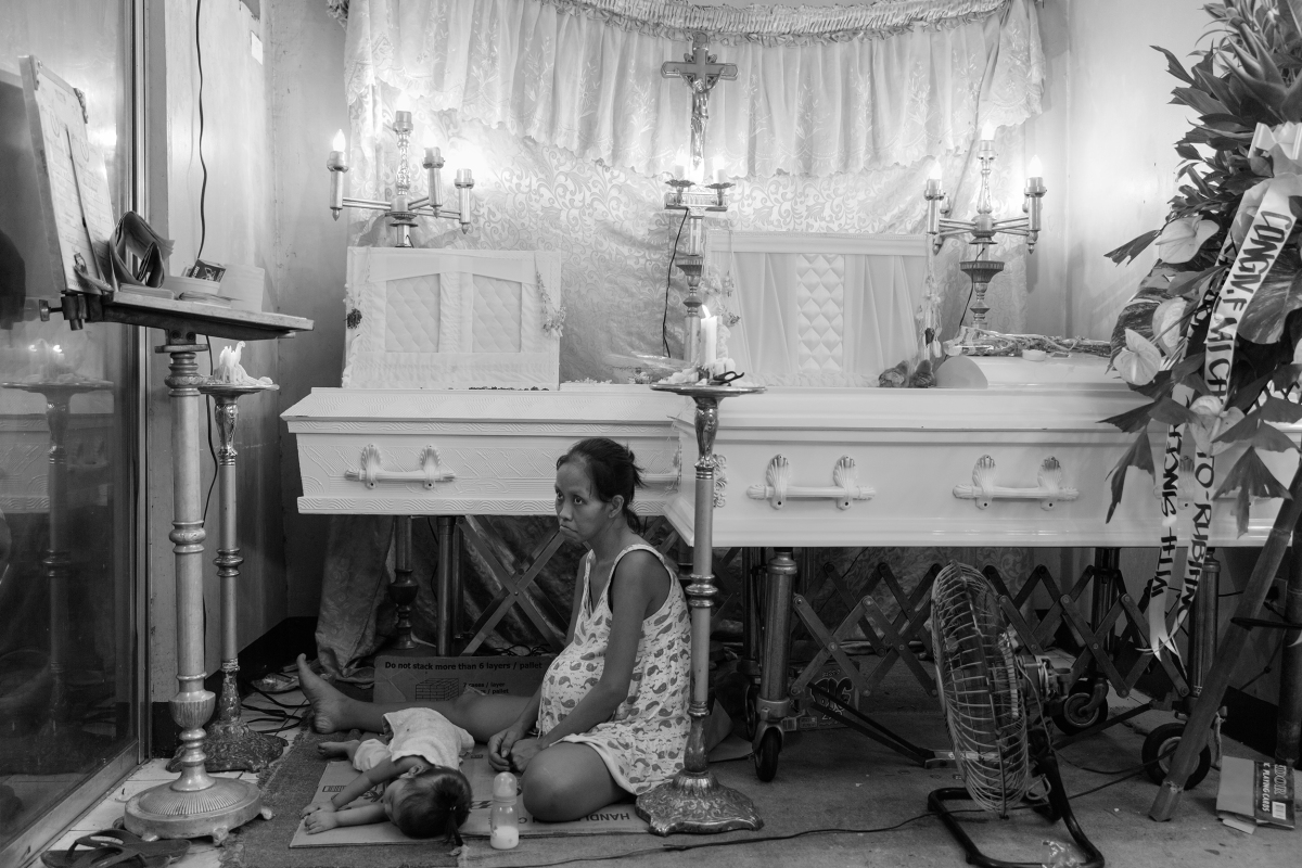 The coffins of Domingo Mañosca and son Francis, 5, on Dec. 14. Both were killed by shots fired through the plywood window of their tiny Manila home. Elisabeth Navarro, nine months pregnant, survived with Erika, 1, and a second girl