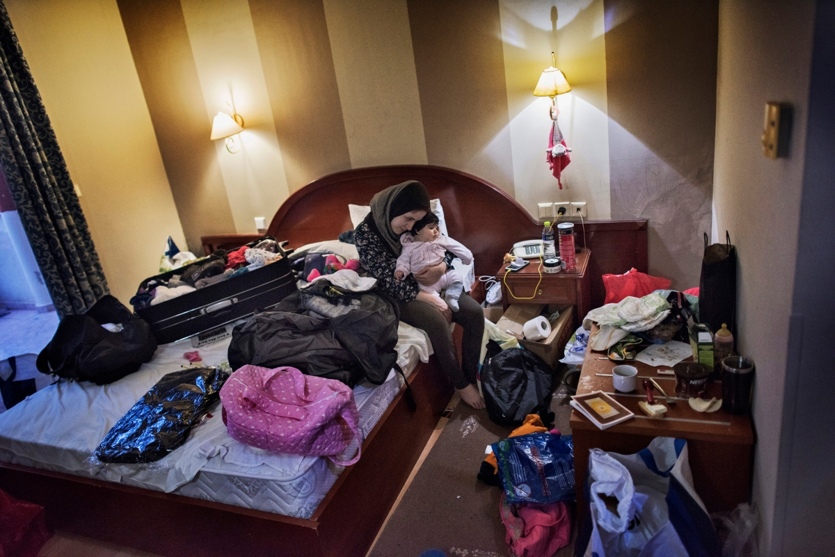 Syrian refugee Taimaa Abazli, 24, cuddles baby Heln, born Sept. 13, 2016, while packing the family's belongings in a hotel room in Giannitsa, Greece after hearing they will have an asylum interview the following morning in Athens, Jan. 19, 2017. Though Baby Heln was diagnosed with an acute bronchial infection and admitted to the hospital, the family decided to check her out out of the hospital as the interview, which they had waited months for, was too important to miss.