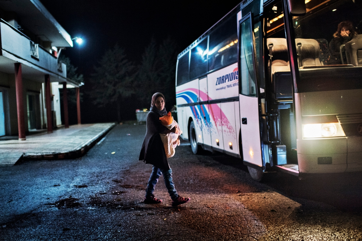 Syrian refugee Taimaa Abazli, 24, carries baby Heln, 4 months old, to a bus sponsored by UNHCR which will take refugee families to Athens for asylum appointments in Athens Greece, Jan. 19, 2017.