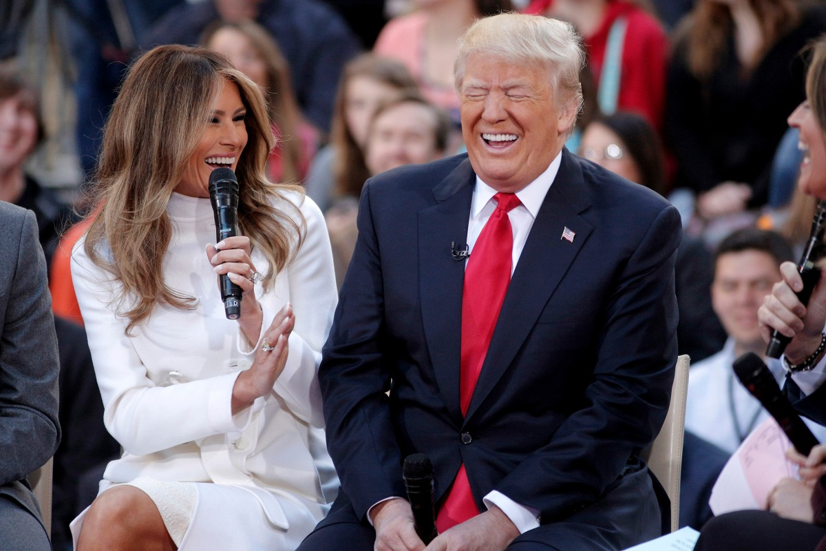 Donald Trump reacts to an answer his wife Melania gives during an interview on NBC's