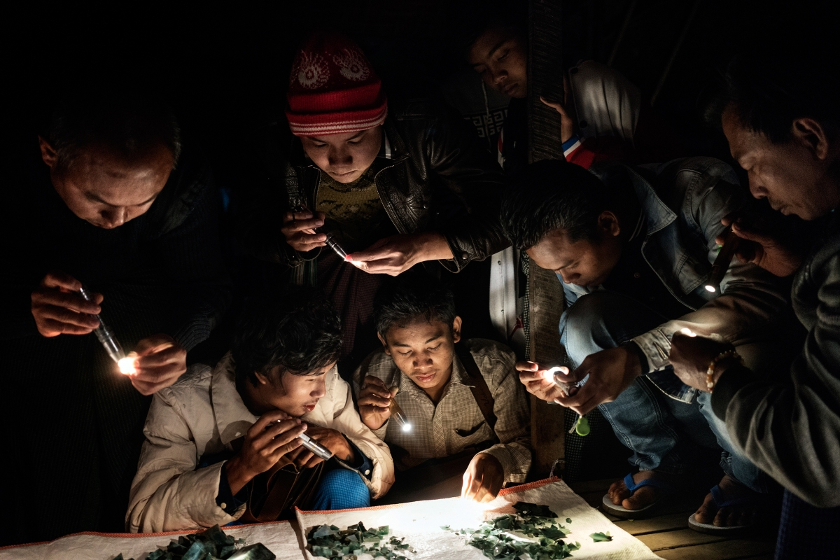 Traders at a market in Mandalay, a city in central Myanmar, use flashlights to examine the color of the jade being sold and to check for cracks.