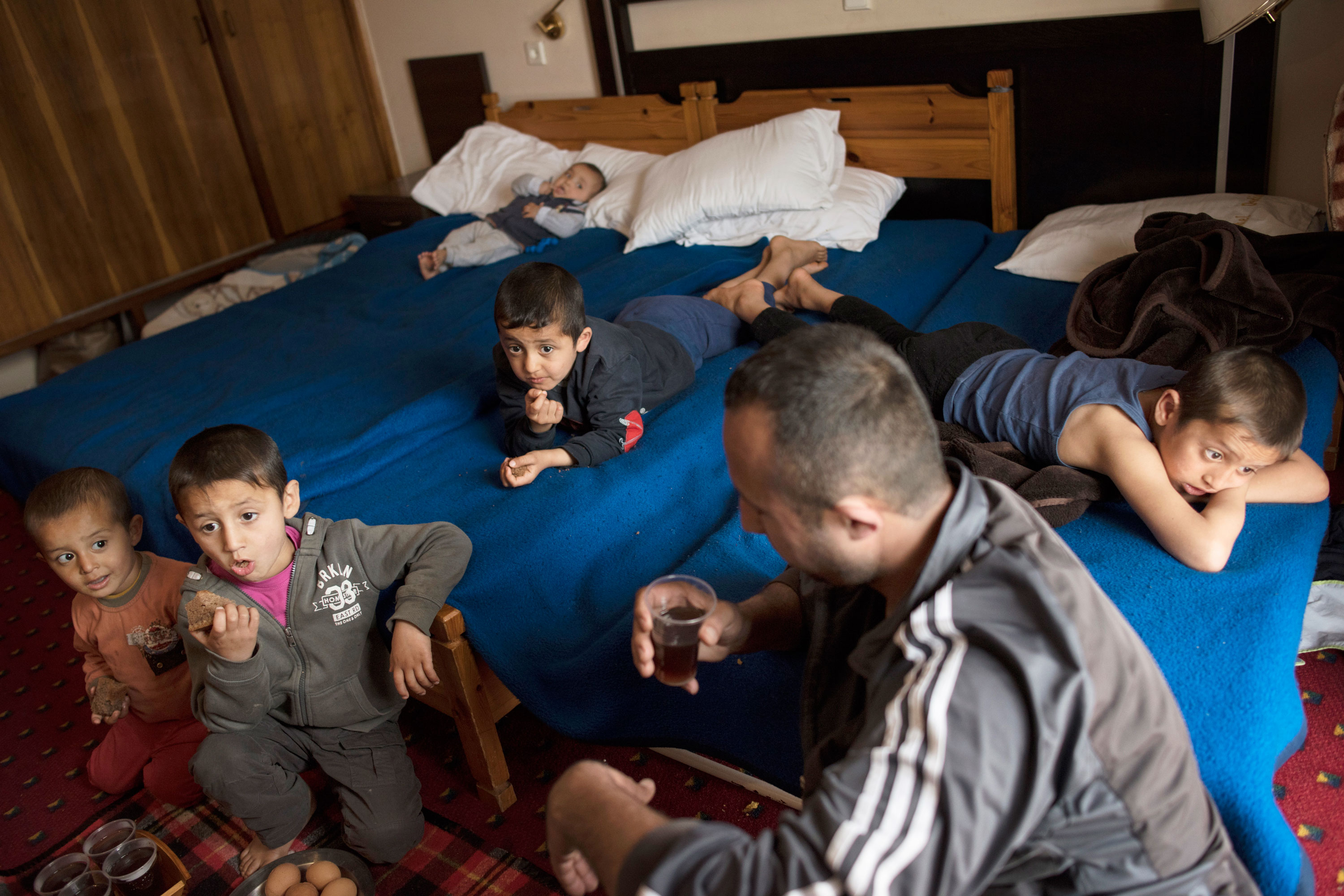 Minhel and the boys watch TV in a hotel room in Kastoria, Greece. Their lives are still in limbo