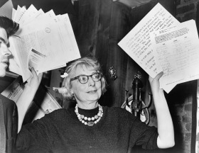 Mrs. Jane Jacobs, chairman of the Comm. to save the West Village holds up documentary evidence at press conference at Lions Head Restaurant at Hudson & Charles Sts