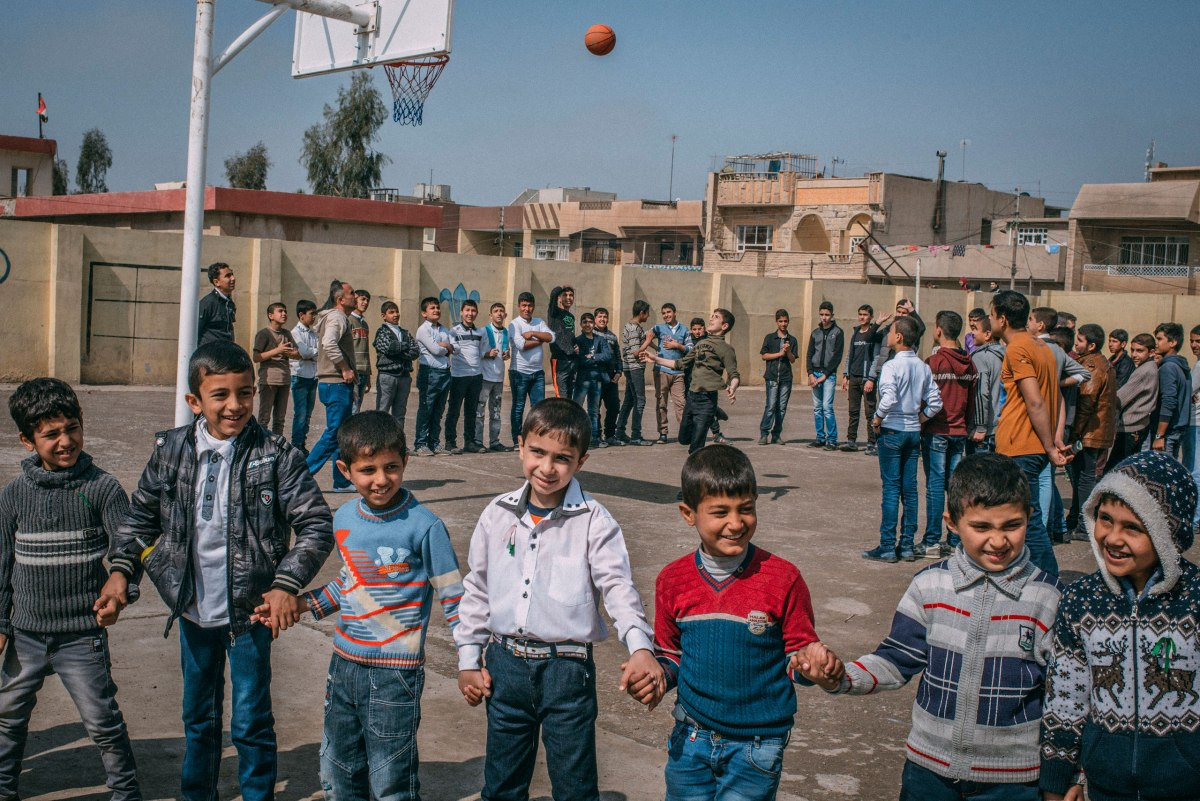 A group of students hold hands while playing in the yard at the Zahret Al-Mada'en school in eastern Mosul on April 2.