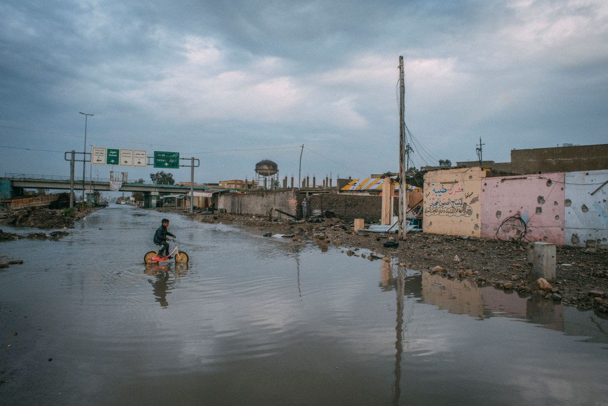 A boy rides a bicycle through floodwaters after heavy rains in the al-Aqeedat district of southwest Mosul on April 1..